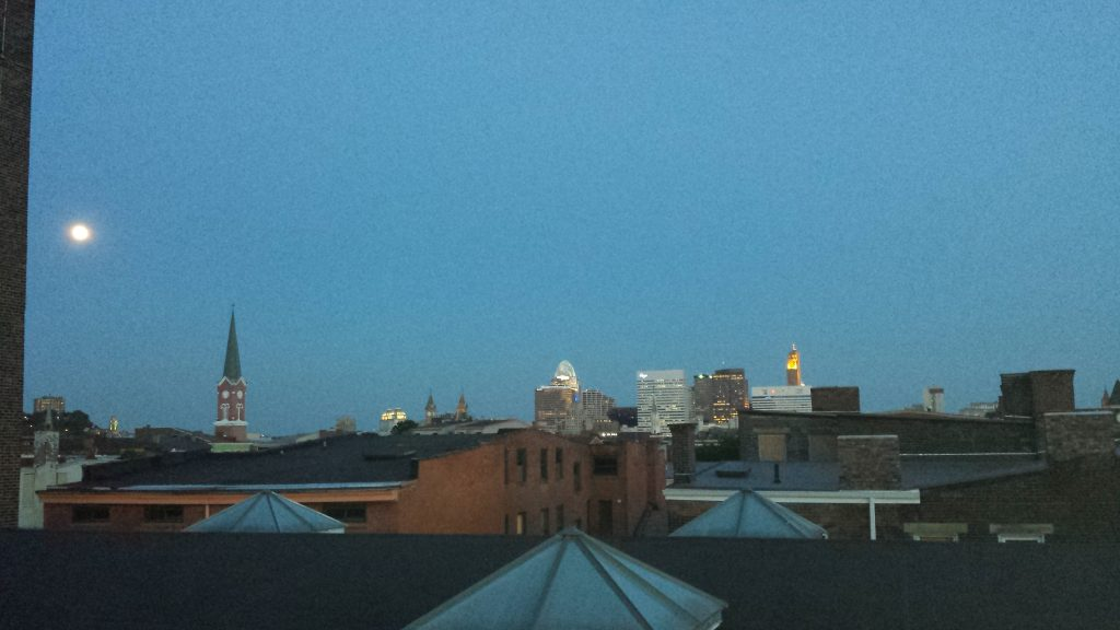 Dusk sets as the moon rises over multiple buildings and skycrappers.