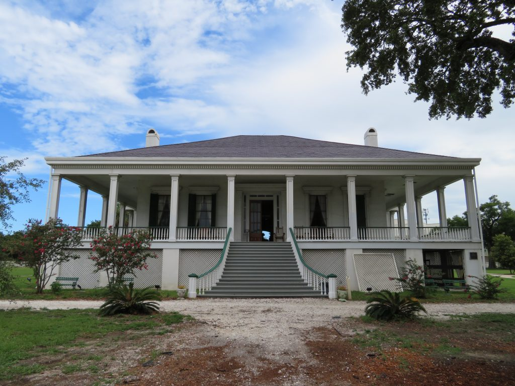 Overview of a large plantation house with a large warp-around porch.