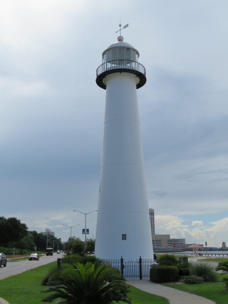 View of a large white lighthouse in the middle of the road.
