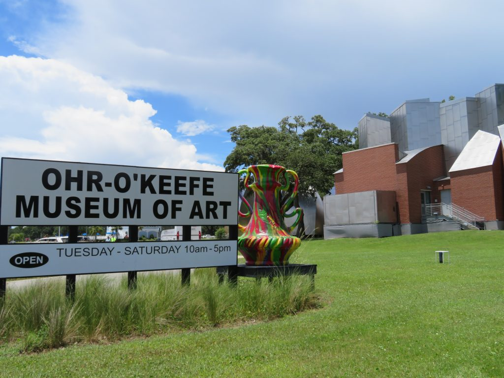 "Large sign says, ""Ohr-O'Keefe Museum of Art"" (one of five family-friendly Mississippi Gulf Coast activities) next to a colorful vase with a large museum complex in the background."