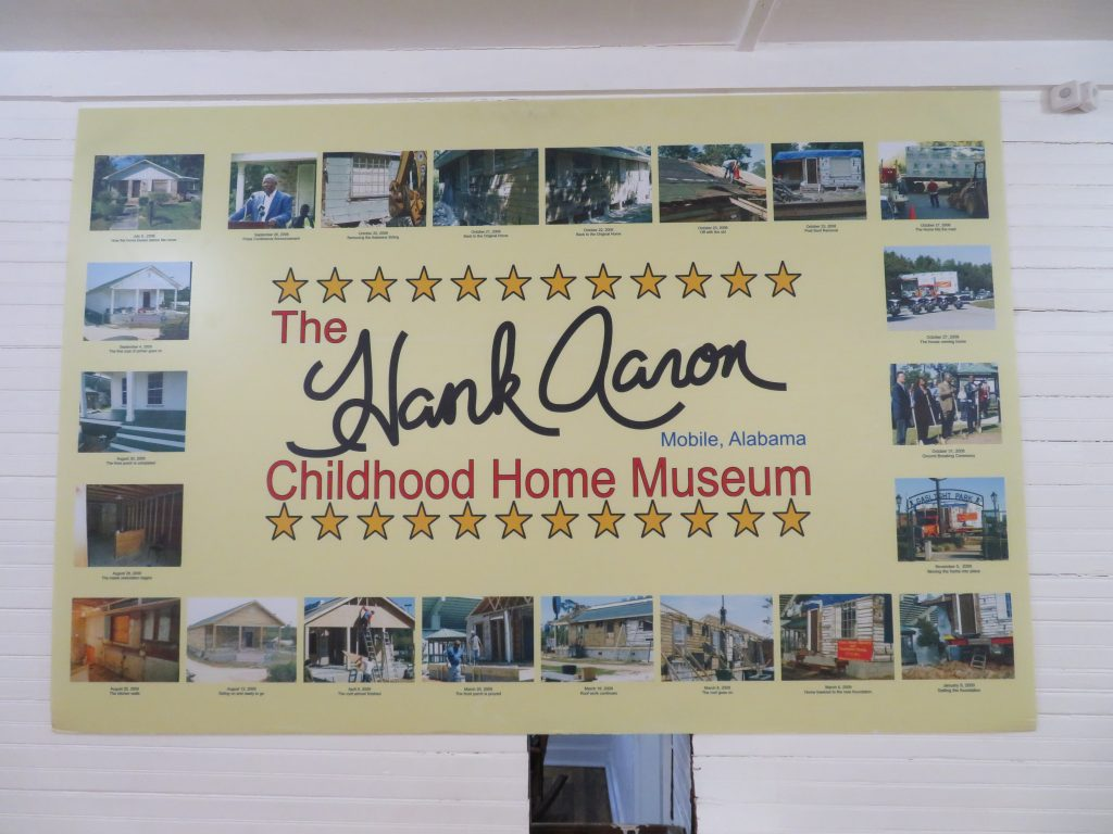 """Sign that says """"The Hank Aaron Childhood Home Museum, Mobile, Alabama"""" with photographs around the text showing the relocation and renovation of the building."""