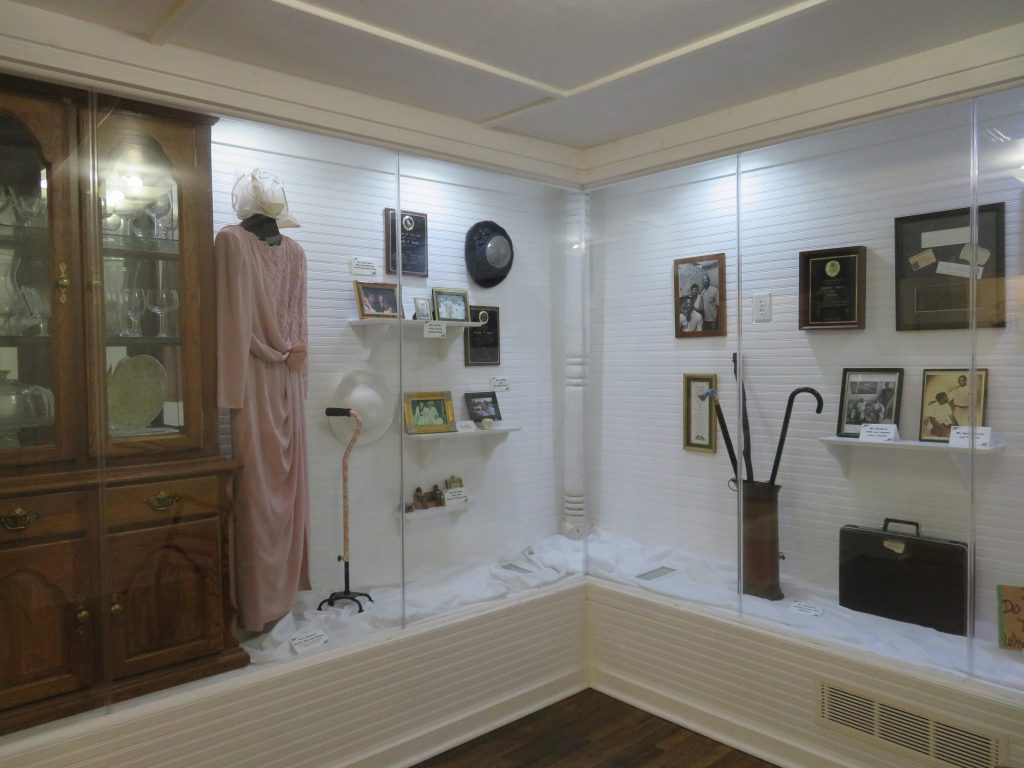 Overview of exhibit at Hank Aaron Childhood Home & Museum showing family items, including a dress his mother owned.