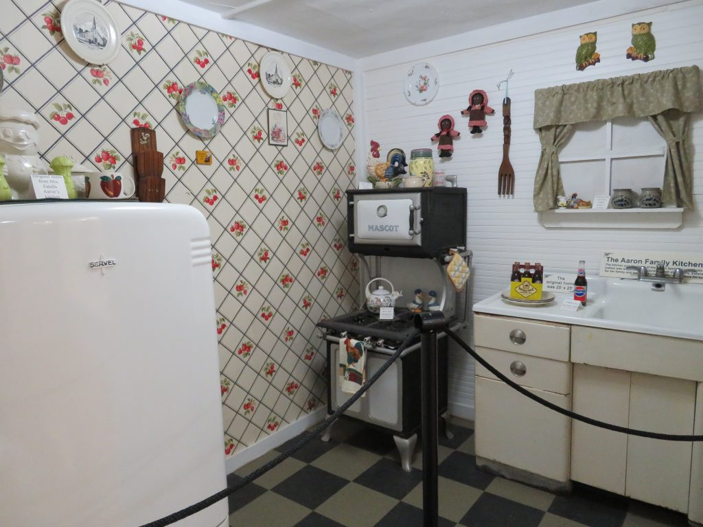 Overview of a small kitchen with a refrigerator on the left, a small wood-fired stove in the back left corner, and a sink on the right.