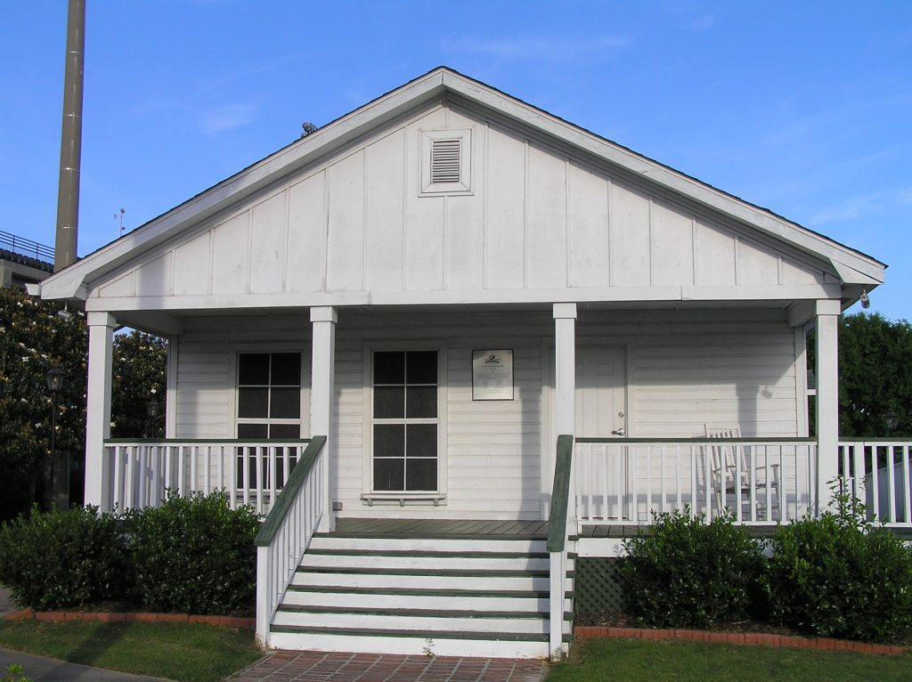 Overview of a small wooden-framed white-and-green-trimmed house with a porch.