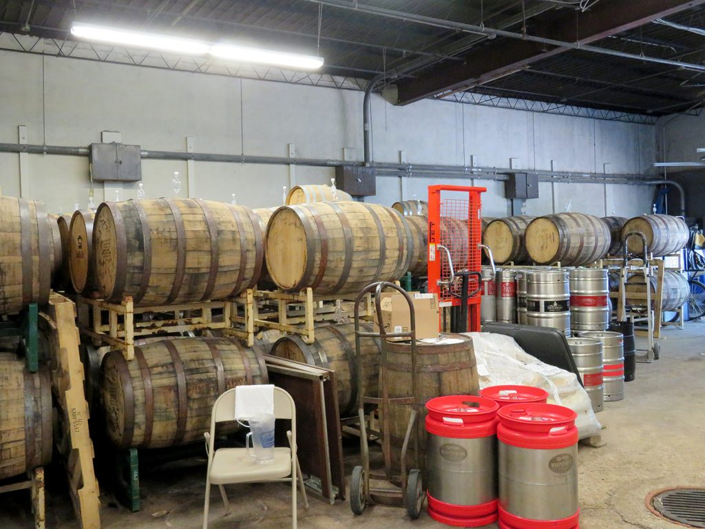 Several wooden barrels stacked on storage racks and some kegs.