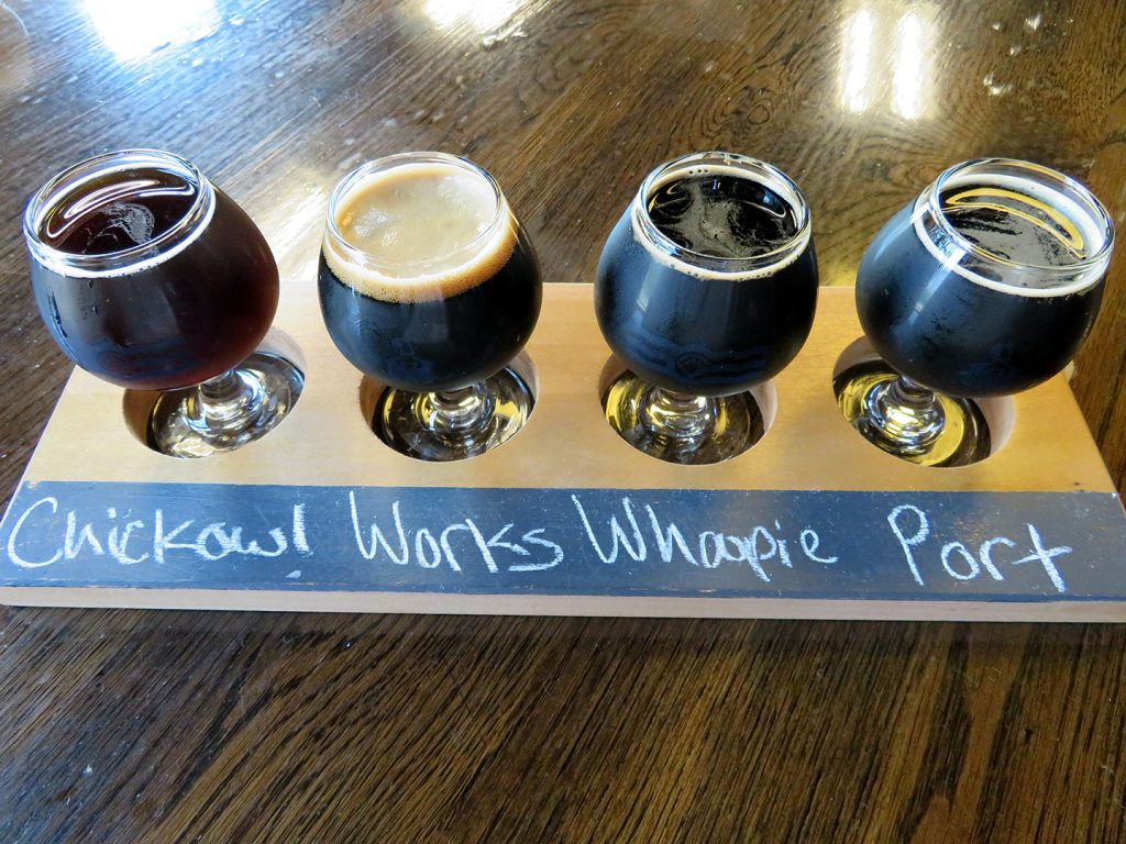 A flight board with four tasters full of dark beers at Listermann Brewing Company.