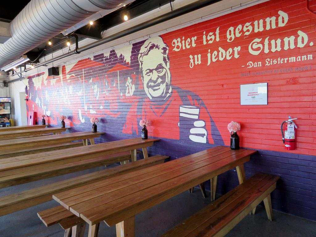 "A large red and dark blue mural with a quote in German from Dan Listermann that translates to ""Beer is healthy at every hour."""