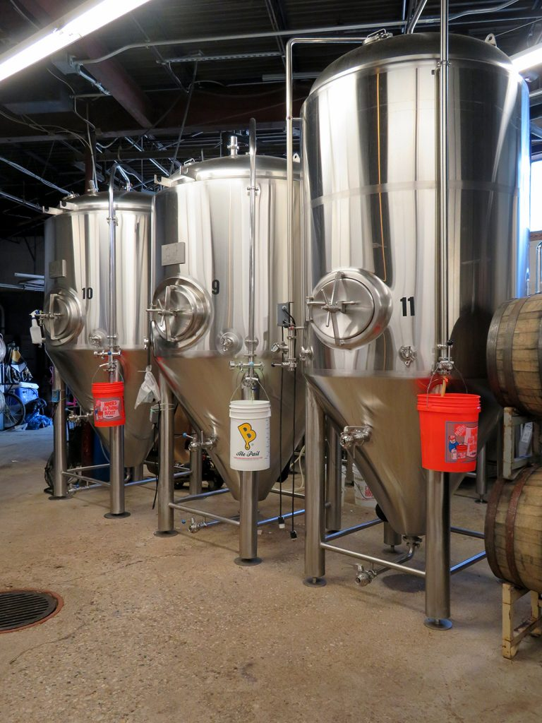 Three steel fermentation tanks stand on the floor at Listermann Brewing Company.