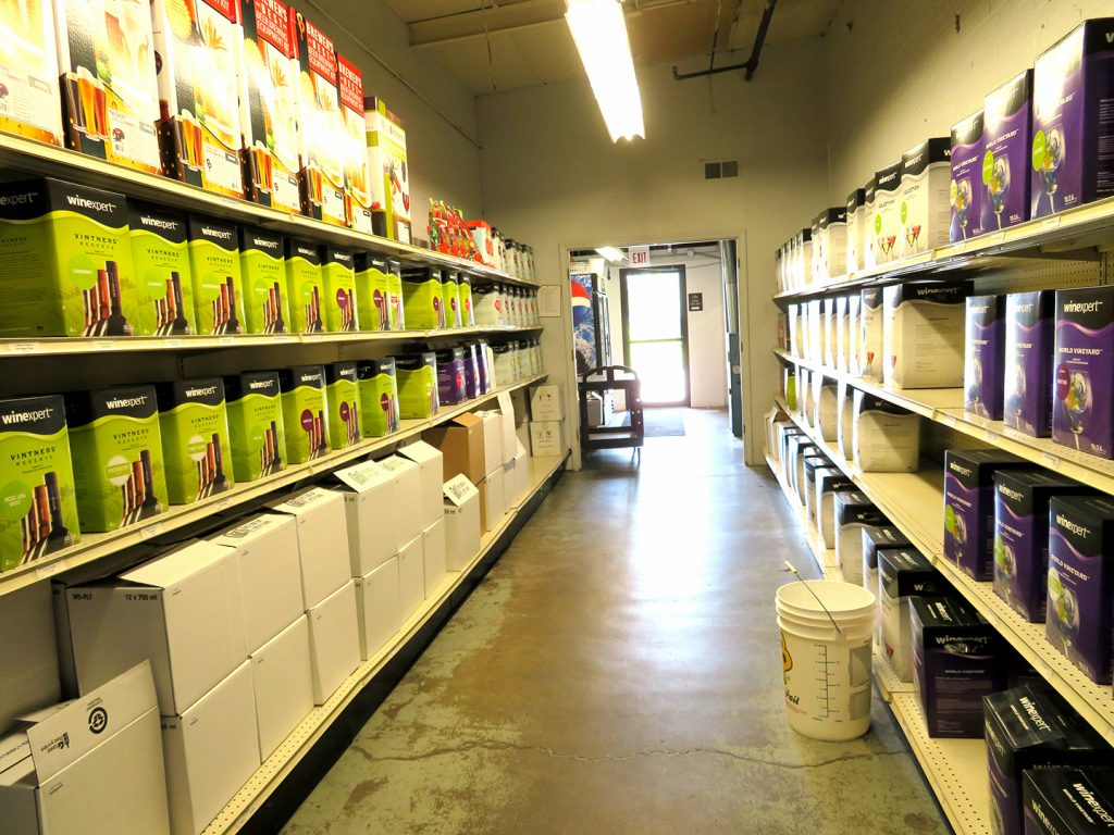 An aisle with wine brewing supplies on shelves.