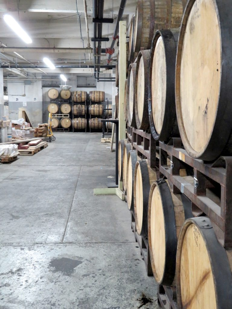 Several wooden barrels are stacked in the background and right-side.