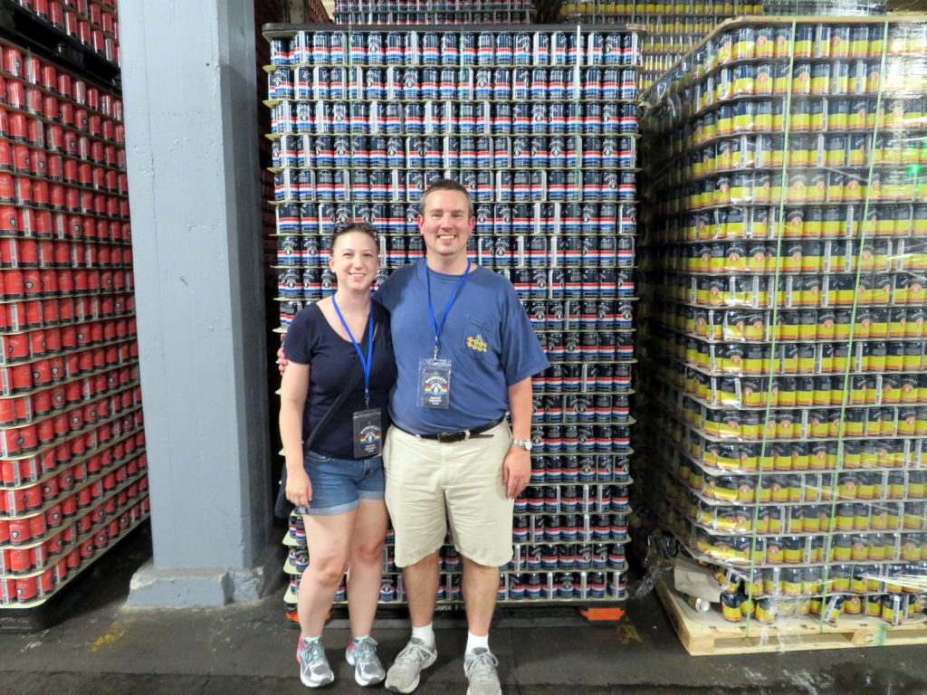 A woman and man stand in front of multiple pallets of empty beer cans.
