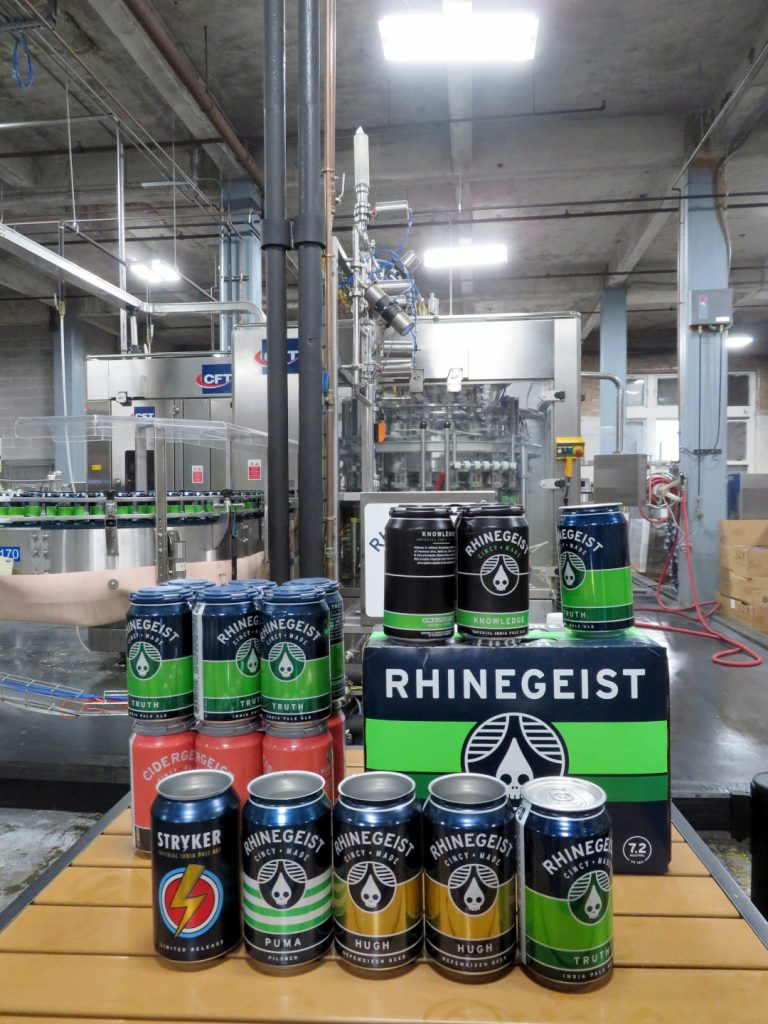 Aluminum cans move through a conveyor belt getting filled with beer.