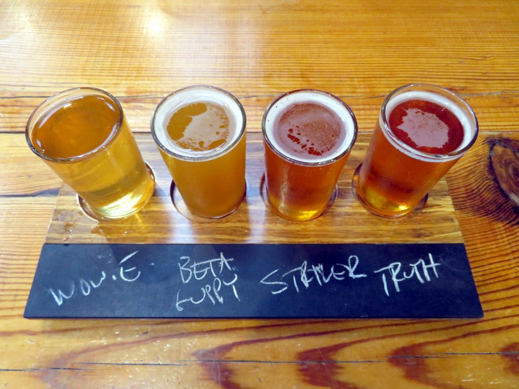 Four tasters of beer on a small flight board.
