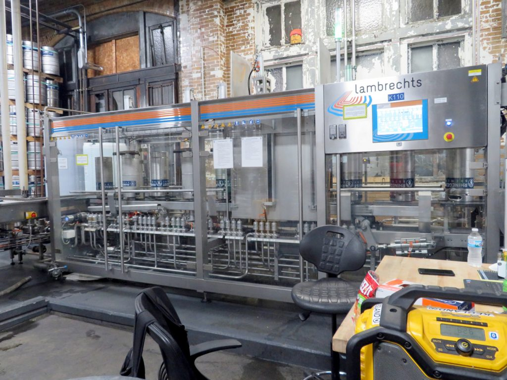 Upside down beer kegs moving through a metal and glass machine for cleaning.