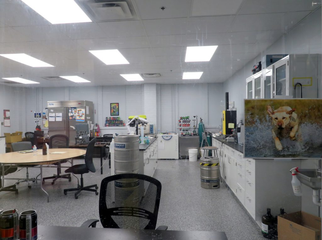 Office space with a refrigerator, multiple counter tops, and a picture of a yellow Labrador retriever running through water.