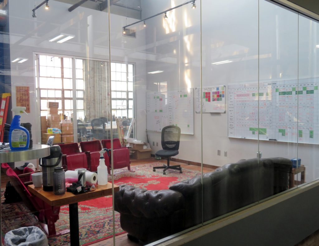 An office with glass windows and two large white boards used for planning beer releases.