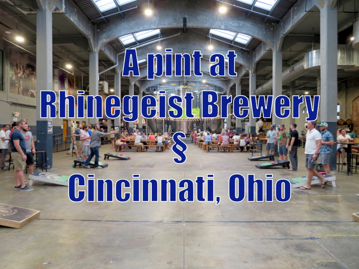 "An open floor space with people playing cornhole and sitting at tables with text on top that reads ""A pint at Rhinegeist Brewery, Cincinnati, Ohio"""