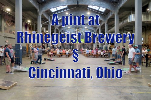 """An open floor space with people playing cornhole and sitting at tables with text on top that reads """"A pint at Rhinegeist Brewery, Cincinnati, Ohio"""""""