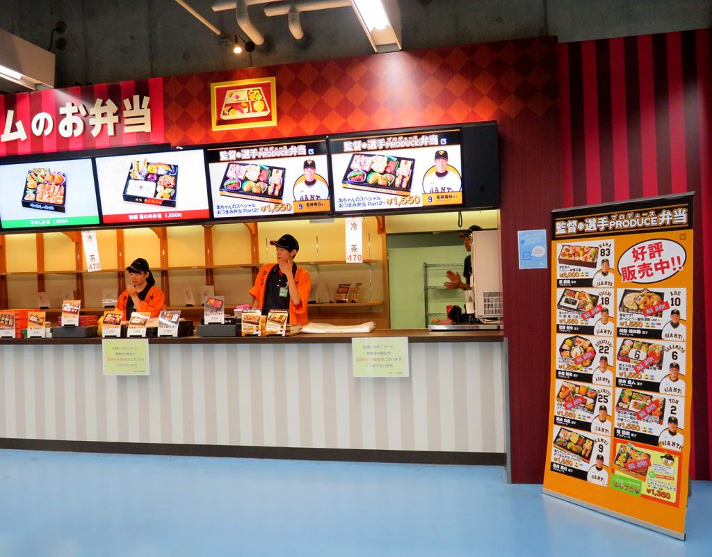 Workers stand at a bento concession stand near a banner with a banner showing Yomiuri Giants players next to specific bento boxes.