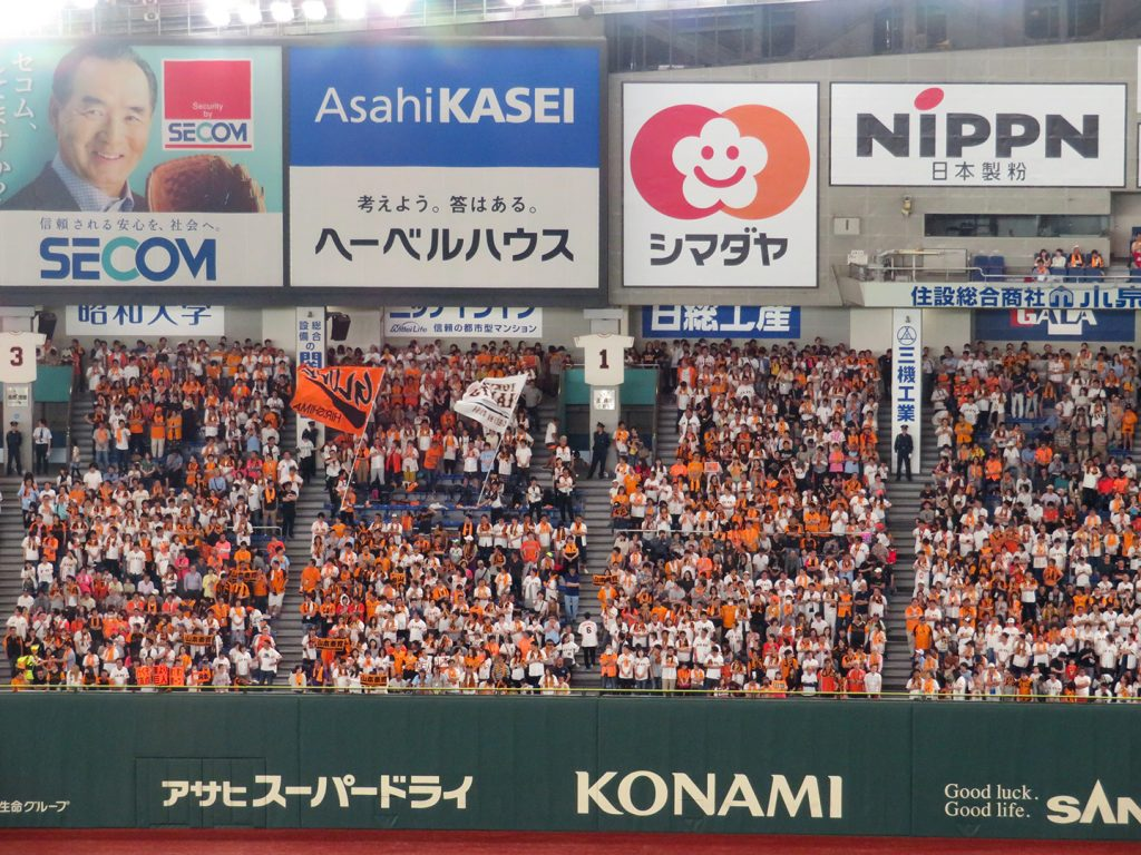 Yomiuri Giants fans wave flags while cheering for their team.