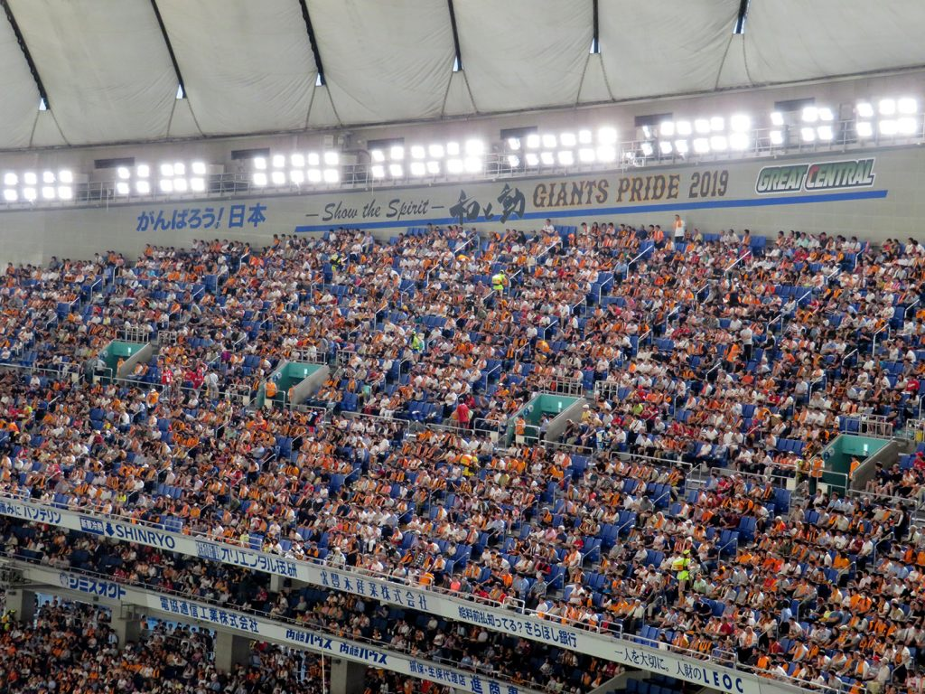 "Text reading ""Show the spirit; Giants Pride 2019"" is written on a wall behind seats at the Tokyo Dome."