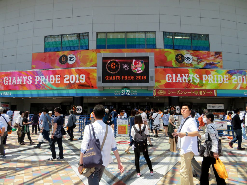 "People stand around the main gate of the Tokyo Dome with a ribbon board that reads ""Giants Pride 2019."""