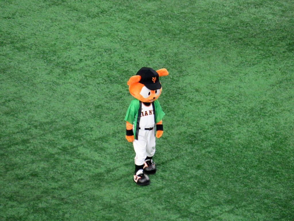 An orange rabbit mascot callled Giabbit stands on a baseball field.