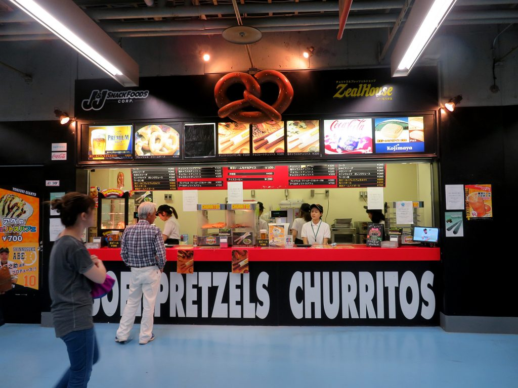 People stand by a concession stand that serves soft pretzels and churritos.