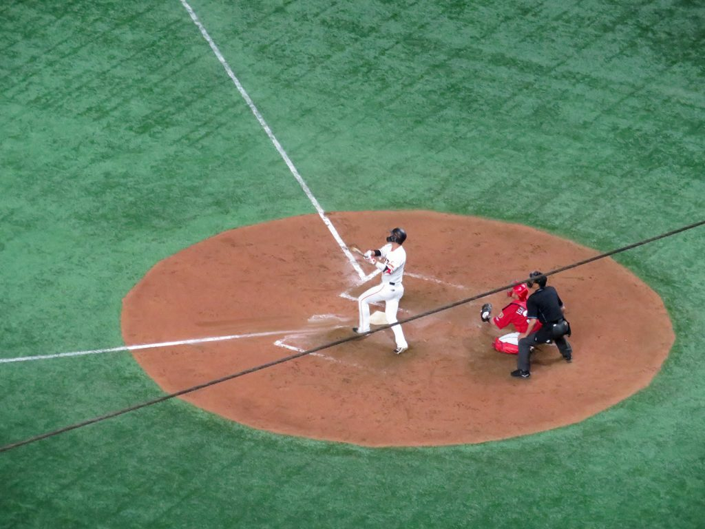 Japanese baseball player Hayato Sakamoto follows through after connecting for a homerun.
