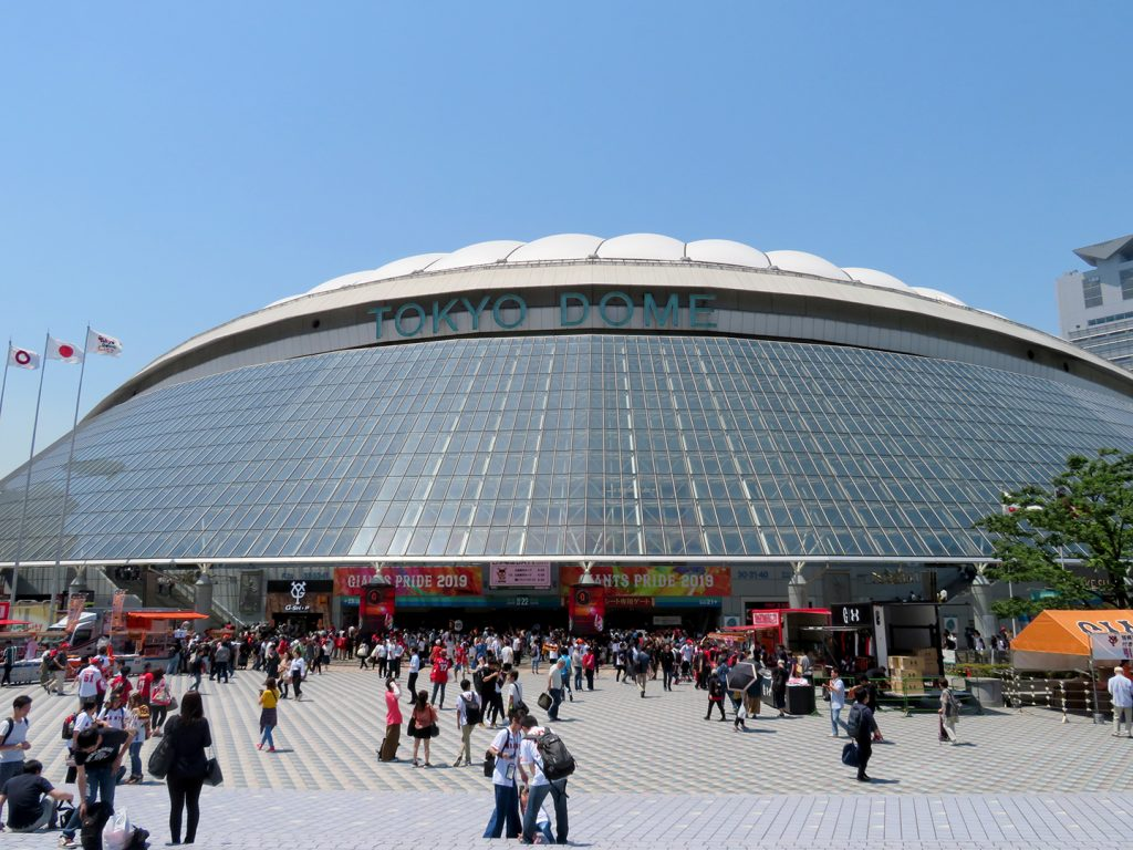 "Domed baseball stadium with glass topped with text reading ""Tokyo Dome."""