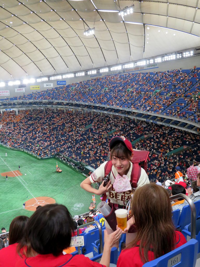 A young woman in a cream-colored baseball uniform with a small keg on her back pours Yebisu beer.