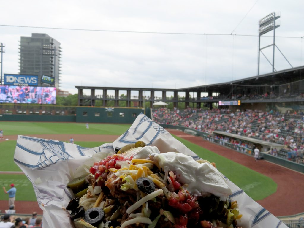 "A loaded set of nachos called the ""Clipper Ship Nachos"" with a baseball field in the background."