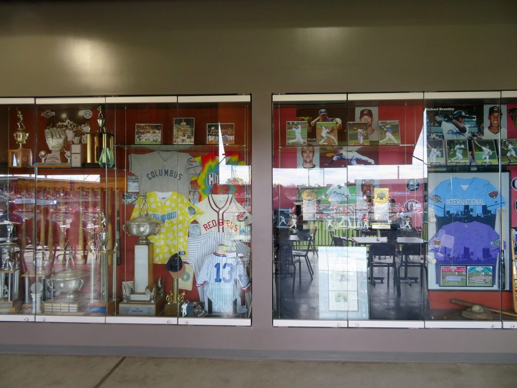 Two glass-covered display cases with numerous pieces of baseball paraphernalia.