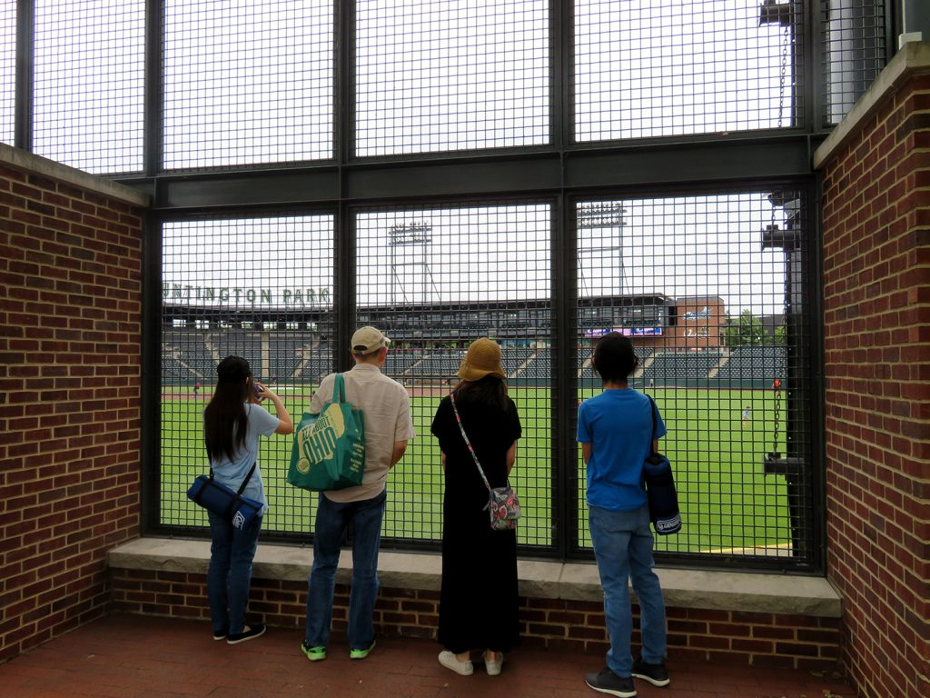 A family of four stand in front of wire fencing to view a baseball field.