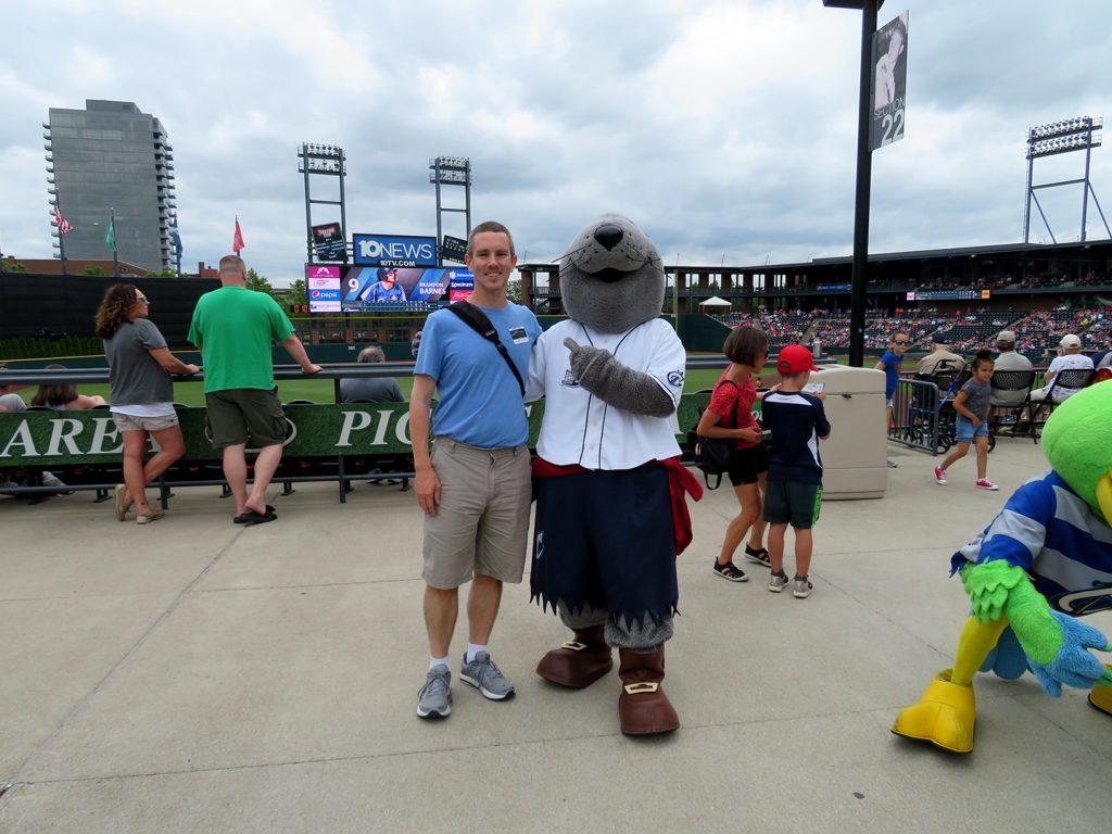A man stands next to a seal mascot.