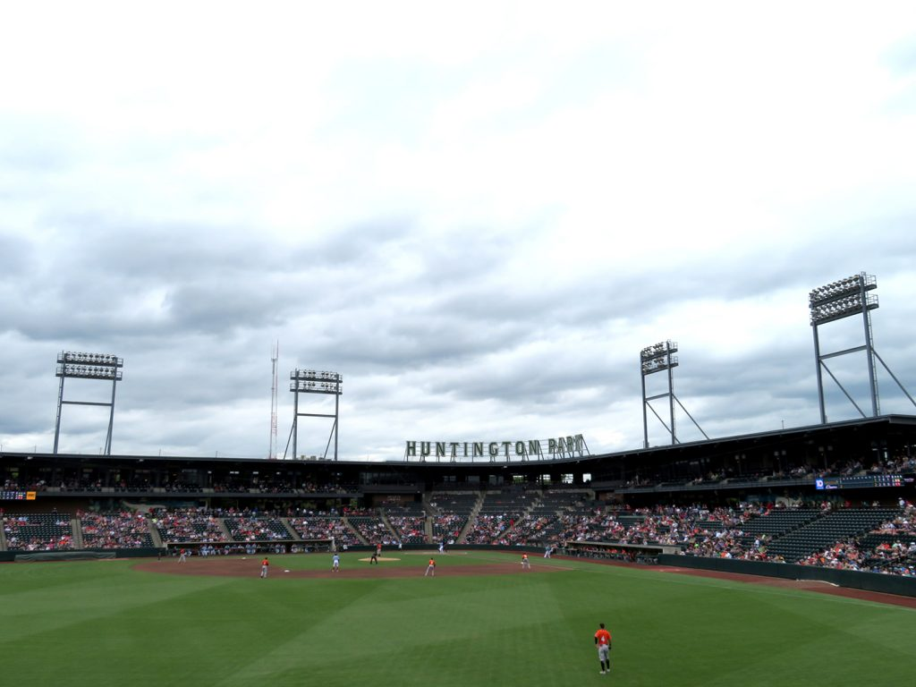 "A view of a baseball field from the outfield with lettering above the home grandstand that says ""Huntington Park."""