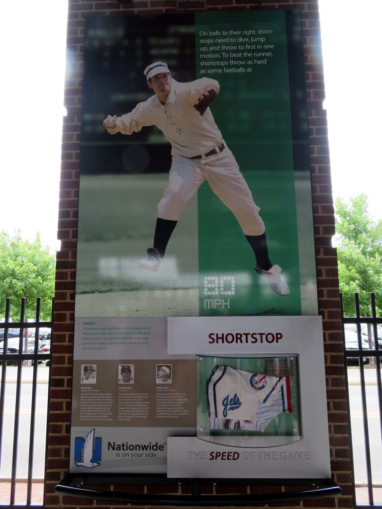 A banner on a brick column featuring a shortstop throwing a ball to first base.