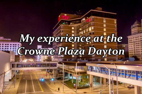 "Nighttime view of tall hotel with text saying ""My experience at the Crowne Plaza Dayton"" overlaying the image."