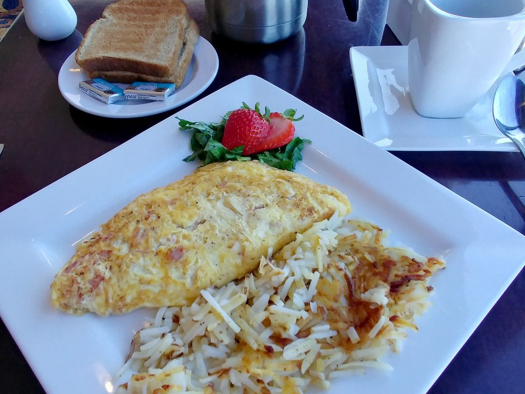 Ham and cheddar omelet next to hash browns on a table with toast to the back left and a coffee cup to the back right.