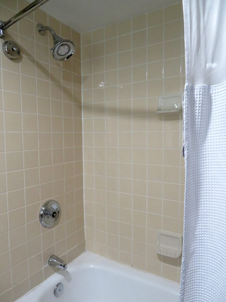 View of small bathtub and shower combination with curtain pulled back to the right.