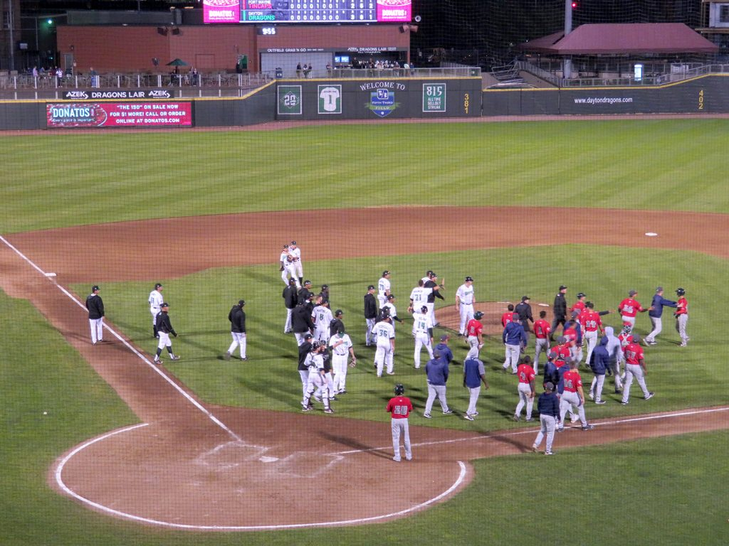 Players from Dayton Dragons on the left and Fort Wayne TinCaps on the right yell at each other on a baseball field.