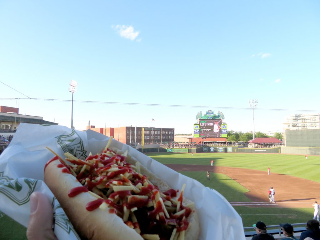 A hot dog covered with fried crisps and sriracha sauce being held in front of a baseball field.