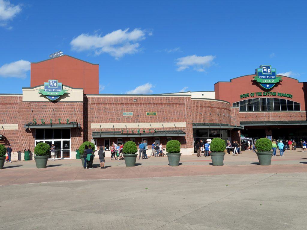 "A large plaza in front of a brick building that says ""Fifth Third Field, home of the Dayton Dragons."""