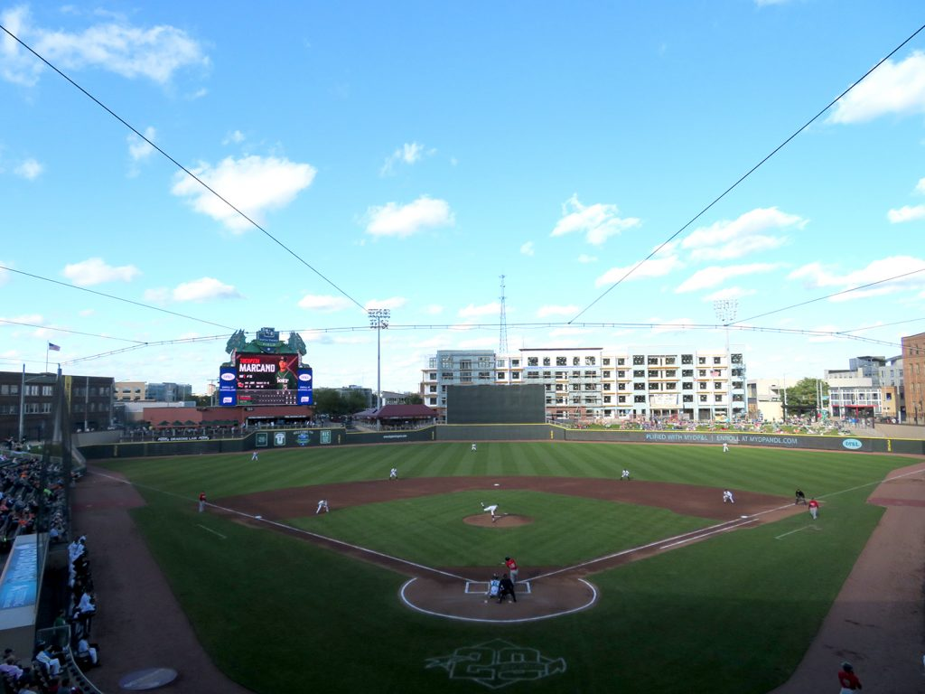 An overview of a baseball field with a videoboard in left field as a pitcher throws the game's first pitch.