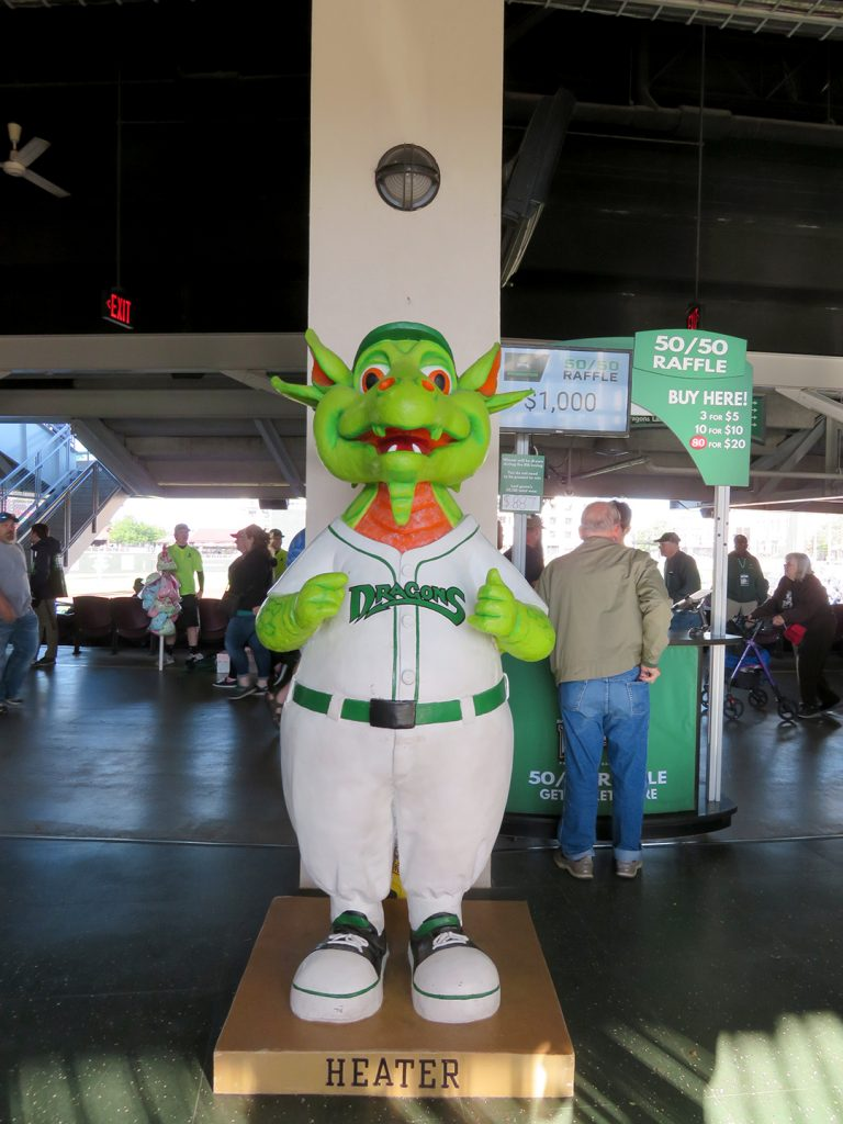 A statue of male anthropomorphic dragon mascot for the Dayton Dragons called Heater.
