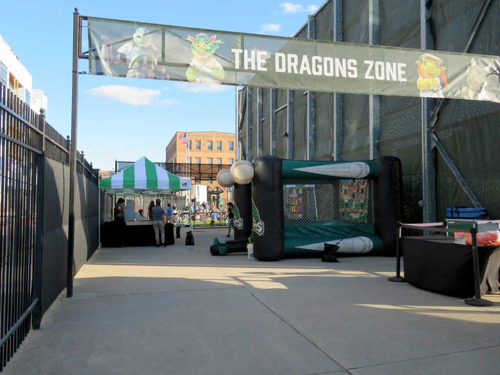 "A banner reading ""The Dragons Zone"" spans a walkway with inflatable play items in the background."