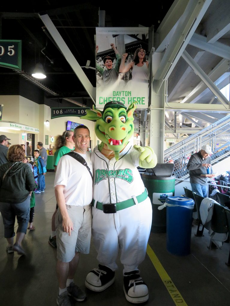 A man stands next to Dayton Dragons mascot Heater, which is a male anthropomorphic dragon.