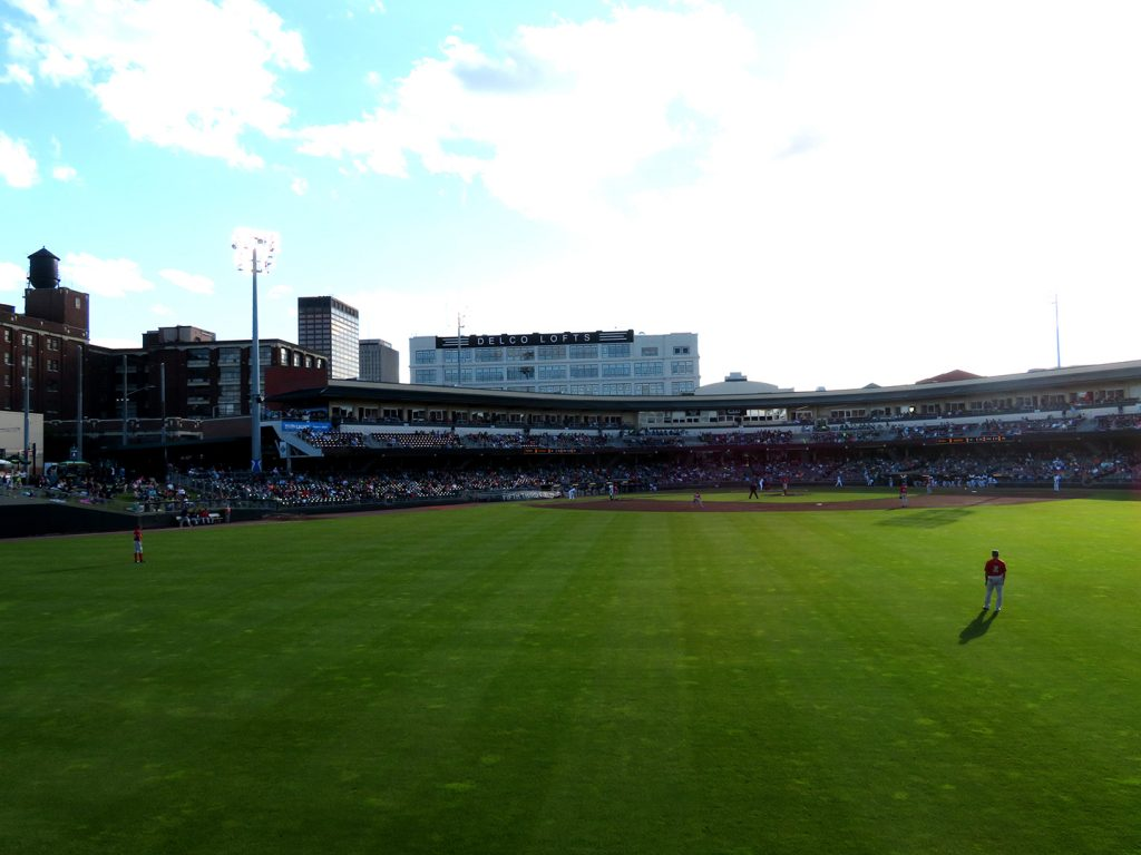A baseball field seen from the outfield with several buildings in the background.