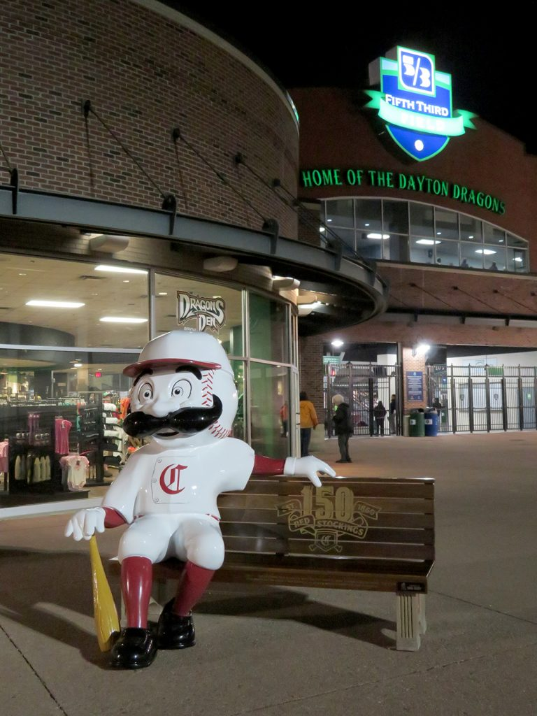 "A bench with a large plastic Cincinnati Reds mascot outside of a brick building that says ""Fifth Third Field, home of the Dayton Dragons."""