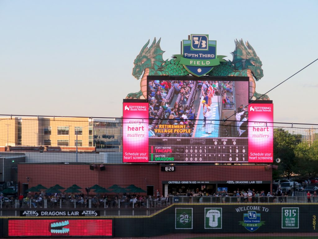 "A large videoboard at a baseball game shows the ""Retirement Village People"" dancing on a dugout."